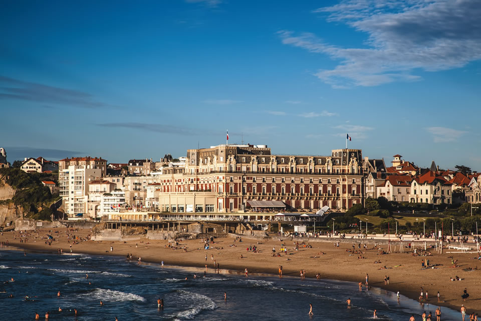 Historical architecture surrounds beachgoers at La Grande Plage in southern France. (Photo by Gregory Guivarch/Shutterstock)